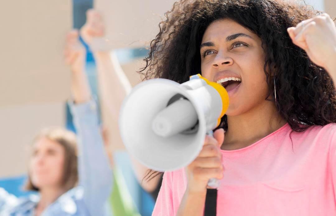 mujer con altavoz en un a manifestacion