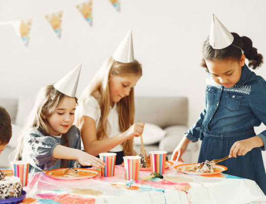 foto de niños y niñas en una fiesta de cumpleaños. llevan gorros, hay banderines y están en torno a una mesa con tartas y comidas sonriendo