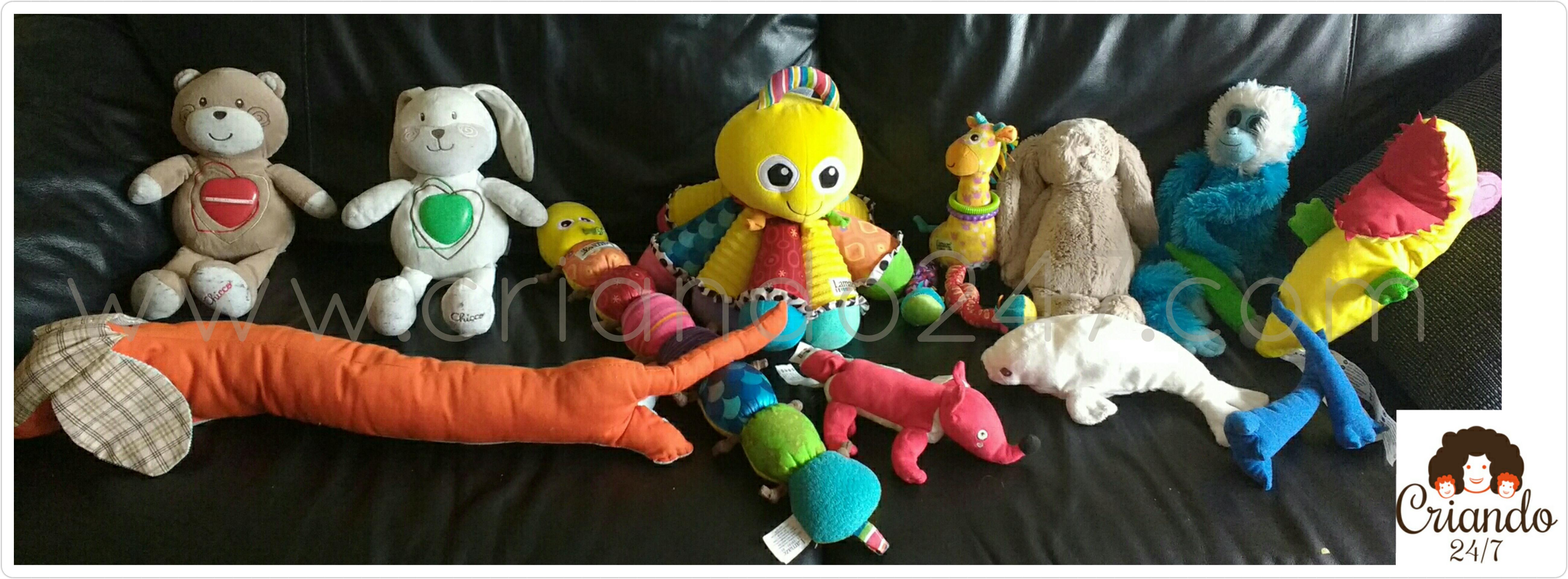muchos muñecos de peluche de colores sentados sobre un sofá de piel color negro