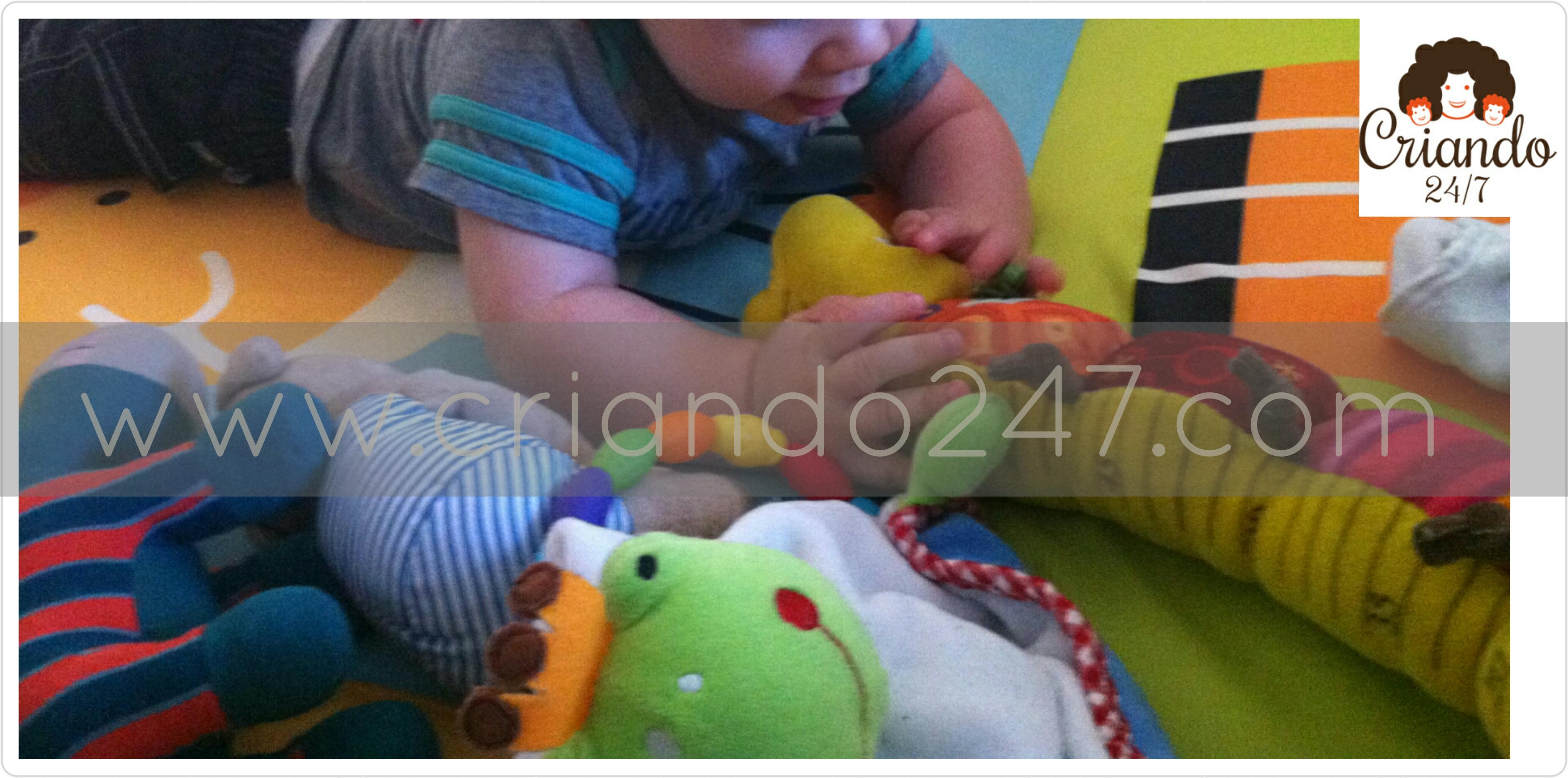 mi hijo con 9 meses acostado en el suelo boca abajo, rodeado de peluches mientras mira y toca uno de ellos con forma de cienpies