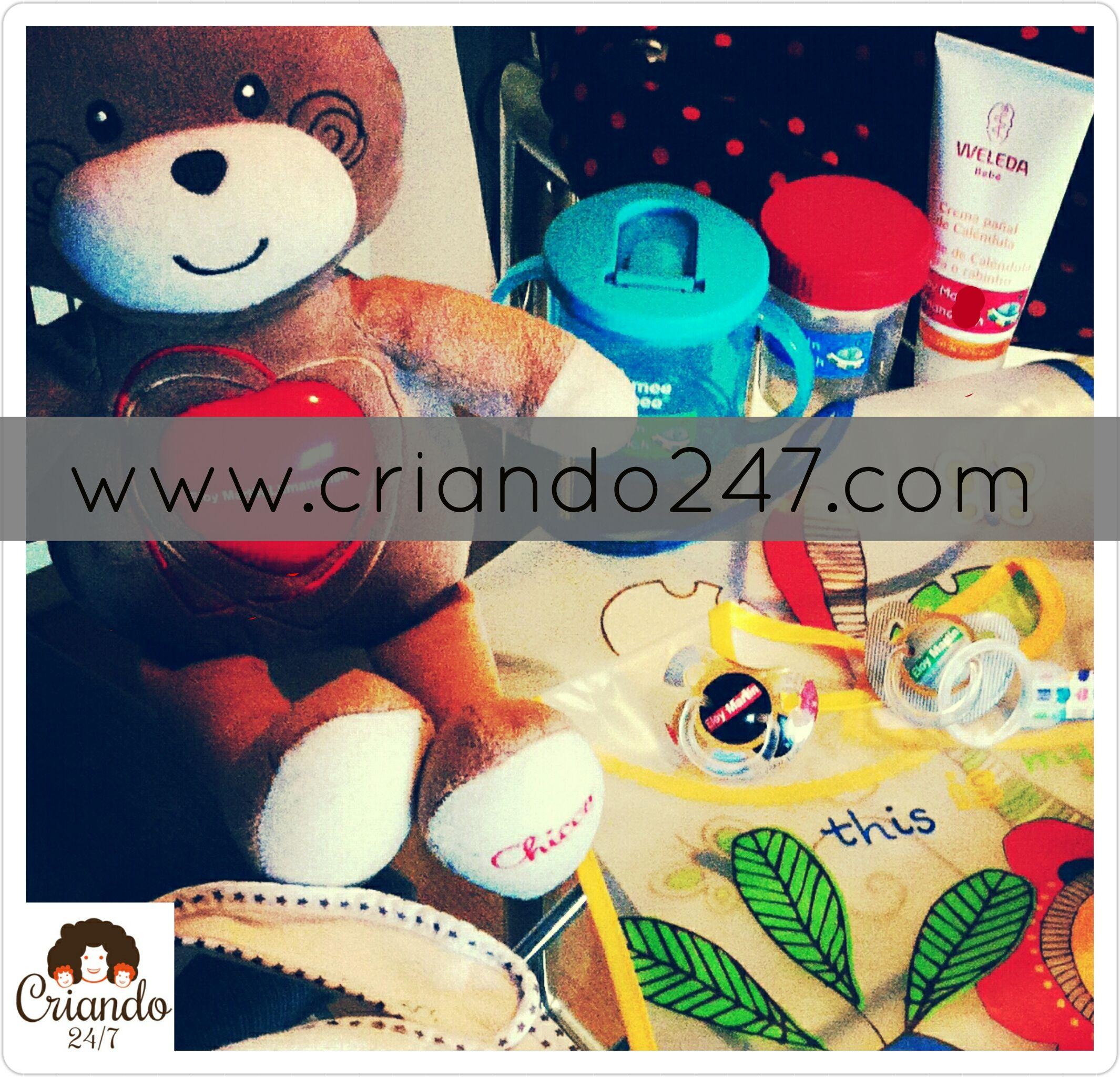 set de cosas para el primer día de guardería sobre la mesa, baberos, chupetes, vasos, crema y un oso de peluche