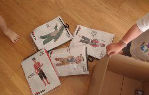 mis hijos sacando disfraces envueltos de una caja