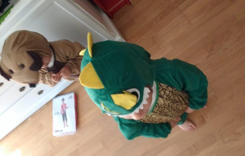 mis hijos de 2 y 4 años disfrazados de perro y dinosaurio en el salón