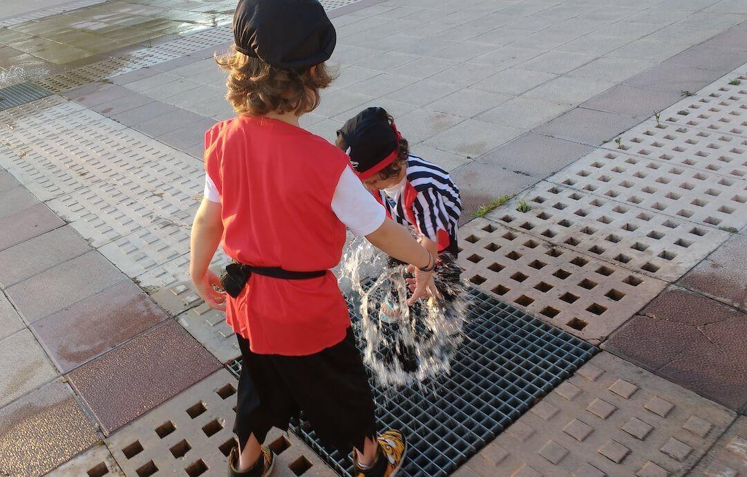 mis hijos de 2 y 54 años disfrazados de piratas jugando en una fuente de la calle