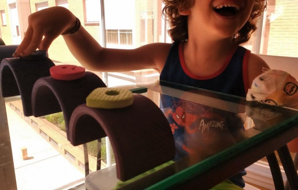 mi hijo en su sesión de terapia restrictiva, colocando letras de goma eva (foam) sobre los arcos del arcoíris grimm puestos en línea. Se lo ve sonreir y que lleva la mano izquierda vendada en puño