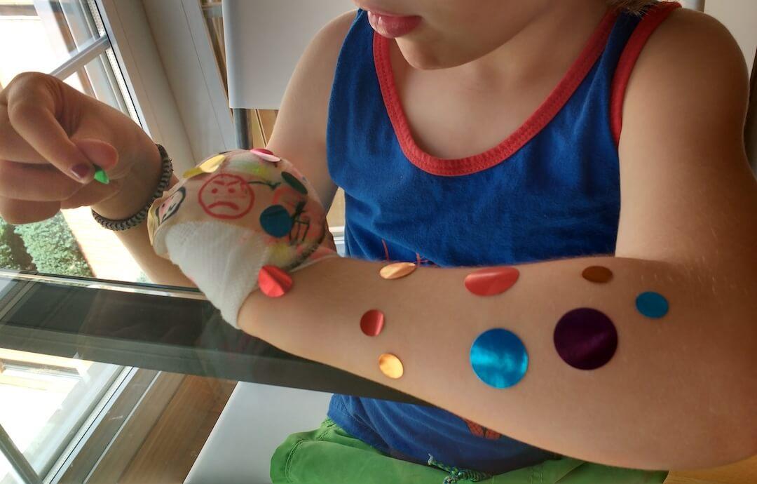 mi hijo con 4 años sentado frente a una mesa despegando gomets de colores de su brazo izquierdo que tiene el puño vendado