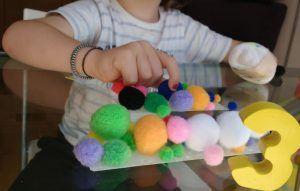 mi hijo cogiendo pompones pegados a la mesa con cinta doble cara. Se ve la otra mano vendada en puño