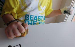 Primer plano de la mano de mi hijo apretando una pelota de plastilina