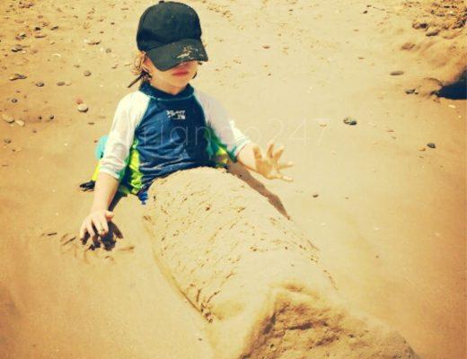 mi hijo sentado en la playa, con gorra y camiseta protectora, y con las piernas cubiertas de arena en forma de cola de sirena