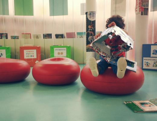 mi hijo menor, con 3 años, sentado en un puff de plastico rojo en la sala infantil de una biblioteca municipal. Está desplegando un libro con pop-ups. A su alrededor se ven cajas de colores con carteles indicando los libros que almacenan en texto y con pictogramas