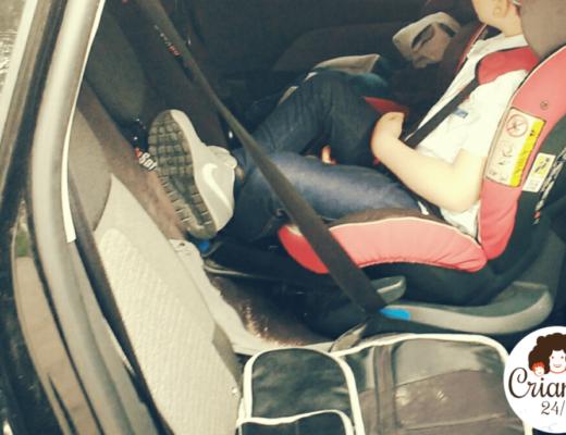mi hijo mayor sentado en una silla acontramarcha en el coche, con 5 años y medio y un percentil 104. logo de criando 24/7