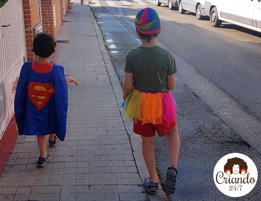 mis hijos de espaldas, caminando por la acera, uno lleva una capa de superman y el otro va con un tutú y una gorra multicolor
