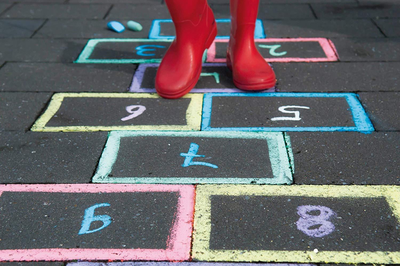 suelo negro con una rayuela pintada con tizas jumbo de colores y unas botas de lluvia rojas caminando por encima