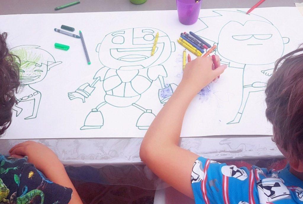mis hijos de 5 y 7 años, de espaldas, sentados en la mesa mientras pintan un dibujo de los teen titans go  que les dibujé sobre papel continuo
