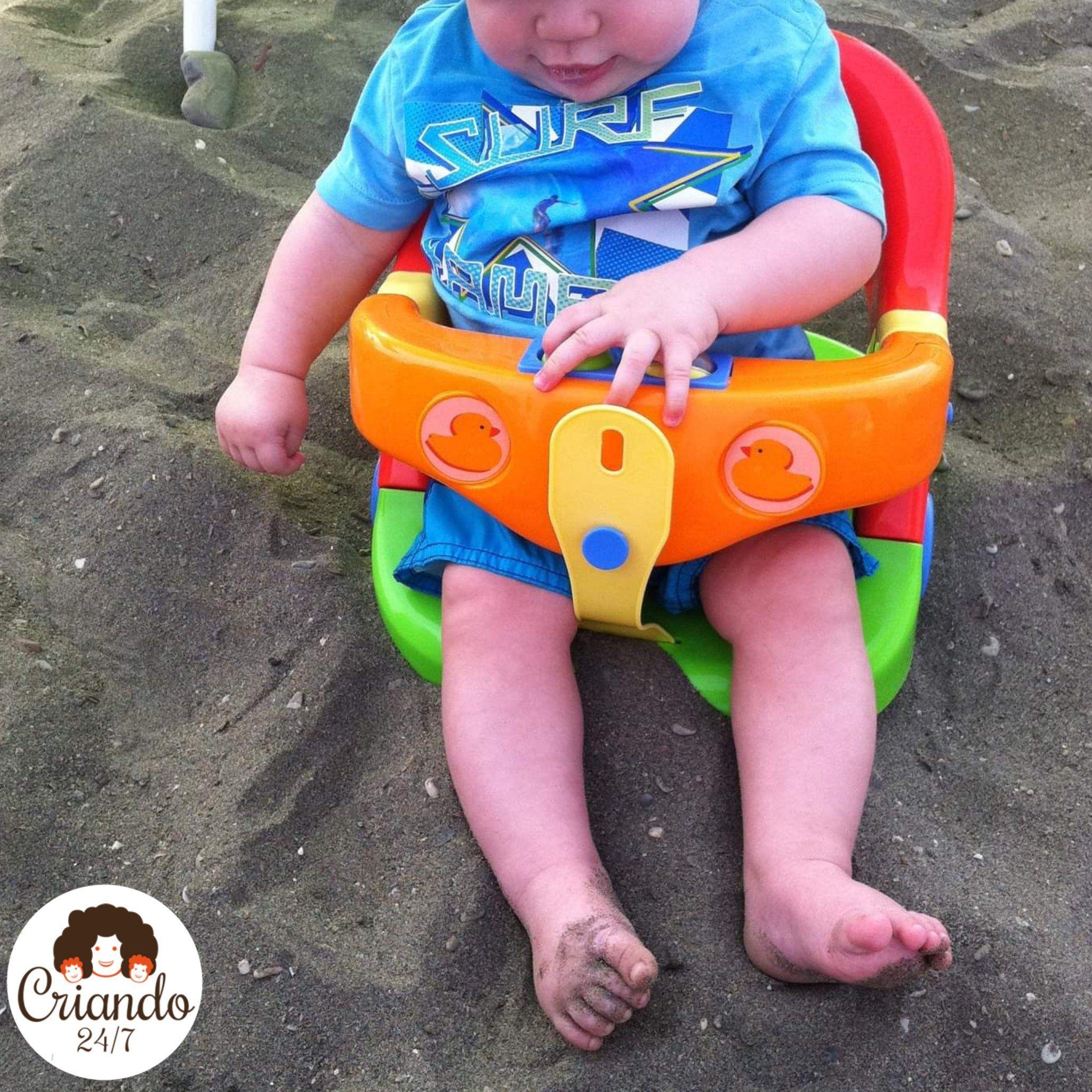Mi hijo con 8 meses, sentado en la playa dentro de un soporte para bañeras ya que de lo contrario se caía hacia el lado derecho.