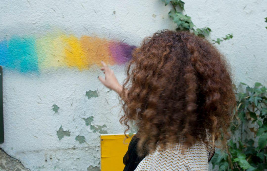 Geraldine de espaldas, señalando un arcoiris pintado sobre una pared blanca
