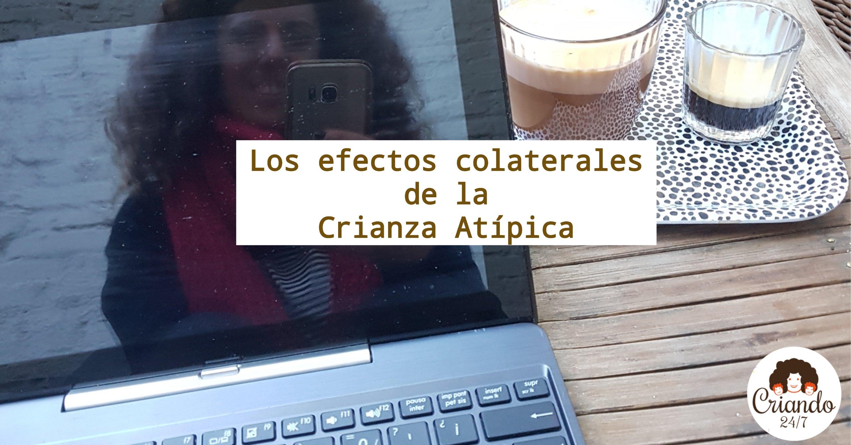 Mi imagen mirando al móvil se ve reflejada en la pantalla del portatil, sobre una mesa de madera con una bandeja con 2 cafés.