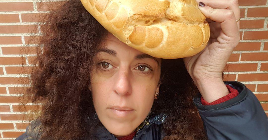 Primer plano de mi rostro sosteniendo una horas a de pan sobre mi cabeza