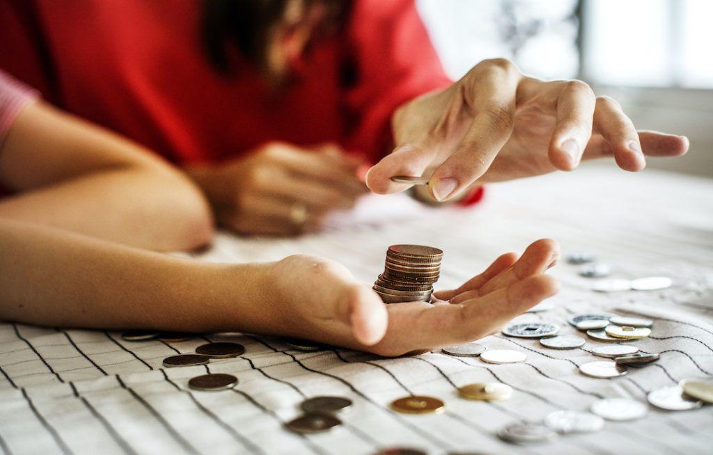 primer plano de manos contando monedas sobre una mesa
