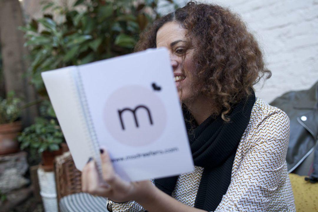 Yo sentada leyendo mi libreta de Madresfera mientras sonrío