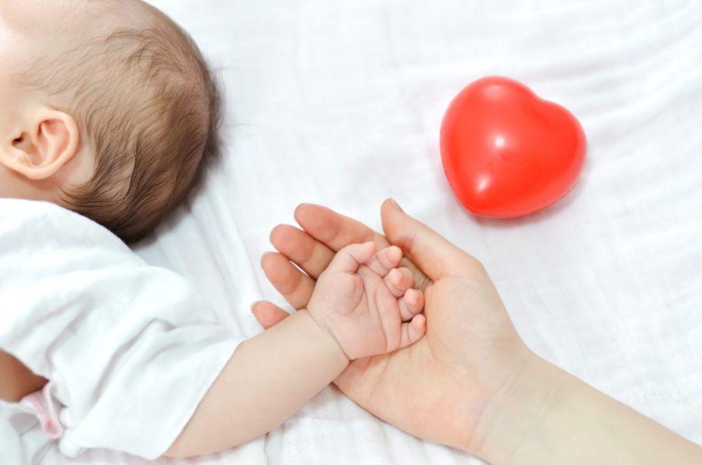 mano de una madre que sostiene la de un bebé recostado sobre una cama de sábanas blancas y un corazón de goma rojo