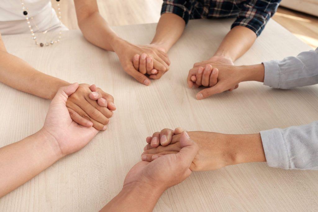 grupo de adultos sentados en torno a una mesa cogiéndose de las manos