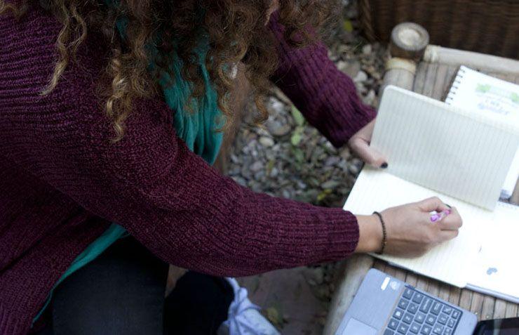 sentada en una terraza mientras escribo en un cuaderno. En la mesa se ve u cafñe , un portatil y un estuche con bolis de colores.