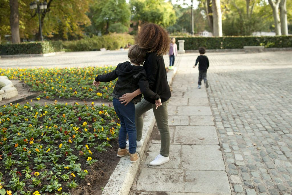 mis hijos de 5 y 7 años y yo caminando de espaldas por el parque del retiro, en madrid,