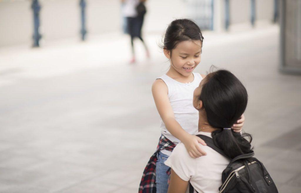 madre en cuclillas habla con su hija pequeña que la mira sonriente
