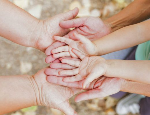 manos de una familia juntas con las palmas hacia arriba