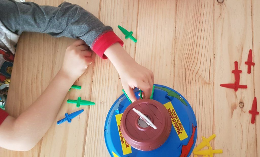 primer plano de las manos de mi hijo de 7 años jugando a Pinche al pirata sobre una mesa de madera. se ve una frutera con manzanas.