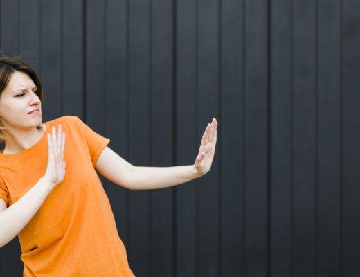 """mujer joven haciendo un gesto de """"para"""" con sus brazos, mientras mira hacia el lado con cara de disgusto"""