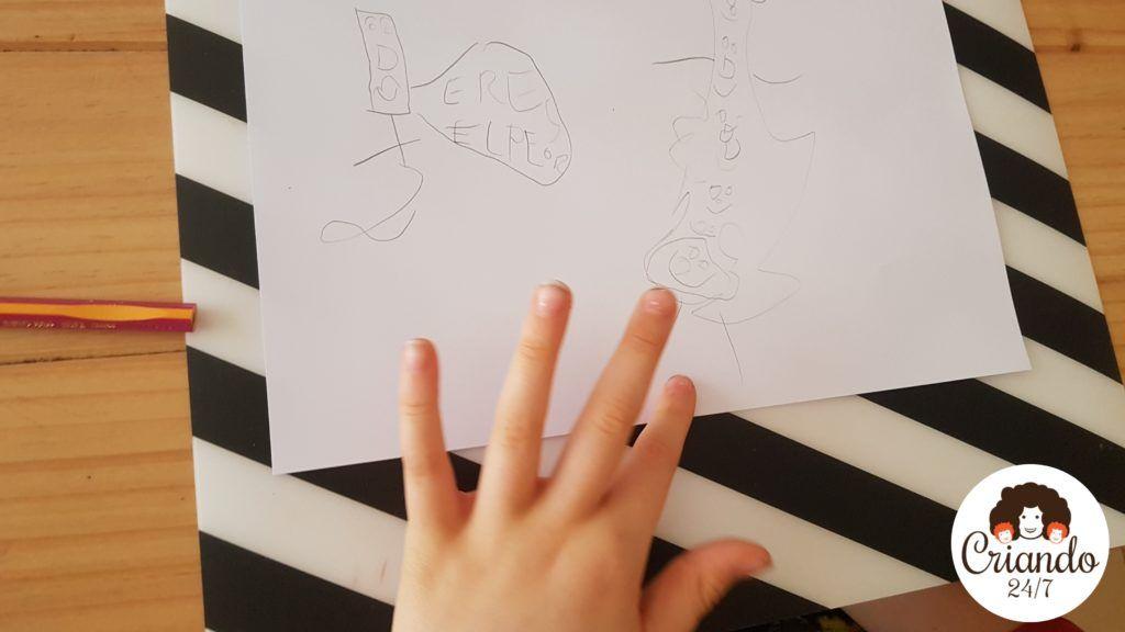 mi hijo de 8 años enseñando el boceto a lapiz sobre un folio blanco de sus monstruos. logo de criando 24/7