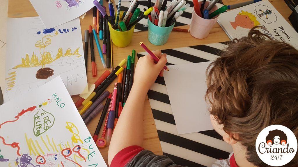 mi hijo de 8 años escribiendo en un folio, rodeado de rotuladores de colores, dibujos de monstruos y el cuento mamá hay un monstruo en mi cabeza