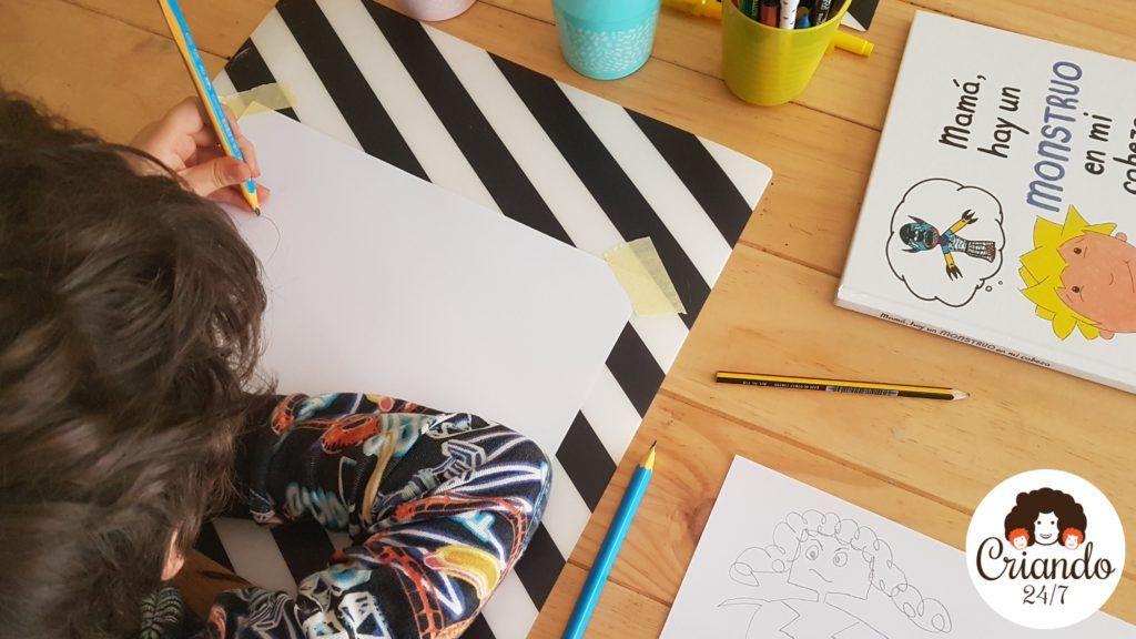 mi hijo de 6 años dibujando con lapiz sobre un folio blanco, a su lado el cuento mamá hay un monstruo en mi cabeza