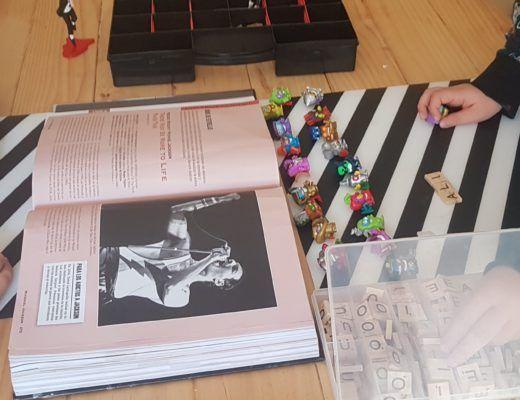 Mis hijos de 6 y 8 años sentados frente a la mesa con un libro de Michael Jackson, superzings y fichas de scrabble
