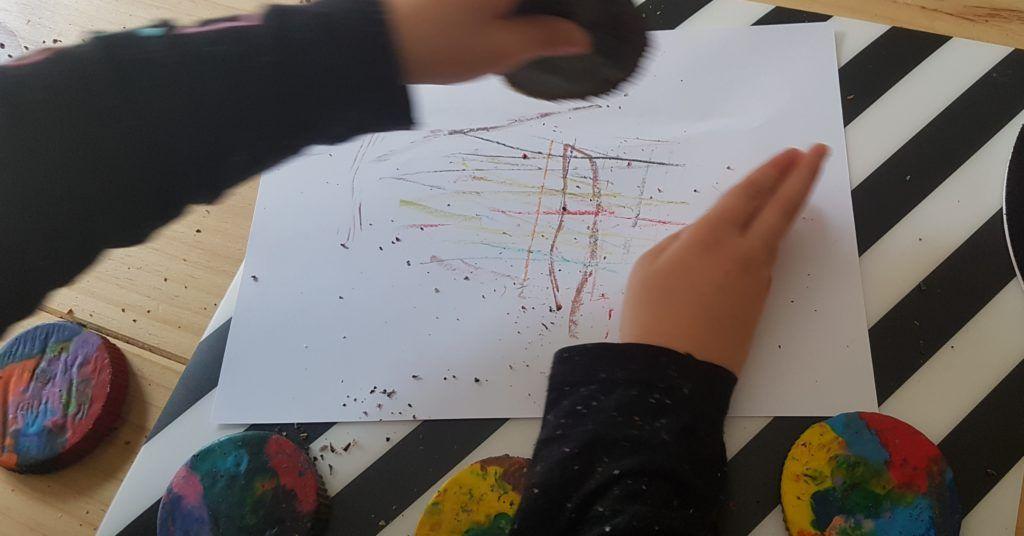 mi hijo de 6 años pintando sobre un folio blanco con una cera reciclada con forma circular multicolor