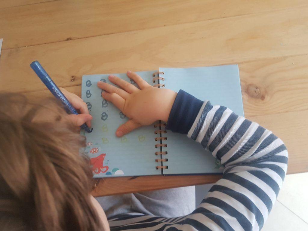 Mi hijo de 8 años con hemiparesia derecha repasando letras B en su cuaderno, sobre las que escribí yo previamente en un color más claro.