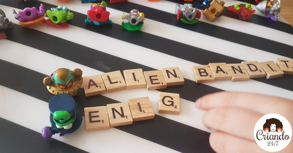 primer plano de superzings , dos de ellos tienen sus nombres escritos con letras de scrabble de madera a su lado: alien bandit y enig (enigma sin completar) mano de mi hijo de 6 años colocando las fichas. logo de criando 24/7
