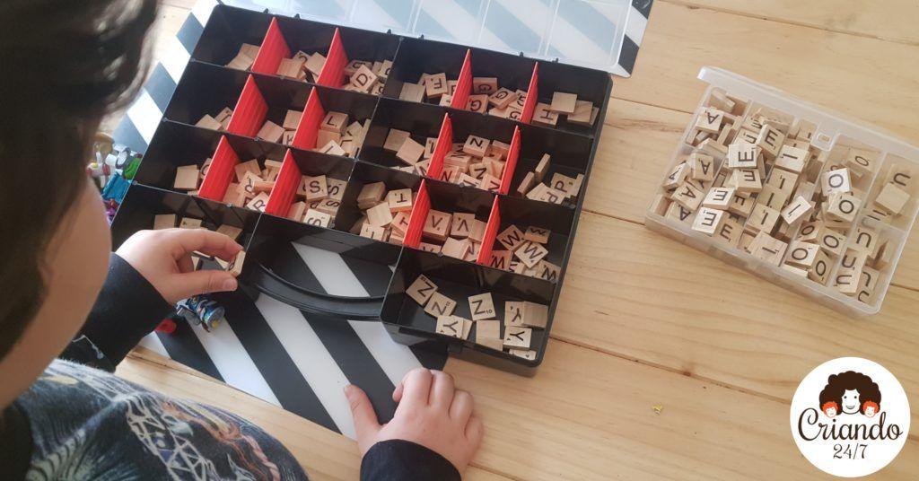 mi hijo de 6 años de pie ordenando letras de scrabble de madera en dos cajas de plástico con separadores. logo de criando 24/7