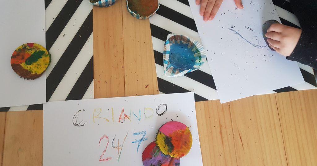 mi hijo de 6 años pintando sobre un folio blanco con una cera reciclada con forma circular multicolor. se ve un folio donde dice criando 24/7