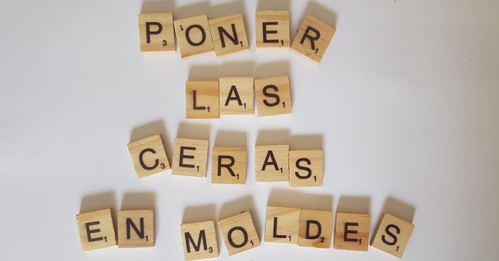 fichas de scrabble de madera formando el texto Poner las ceras en moldes.