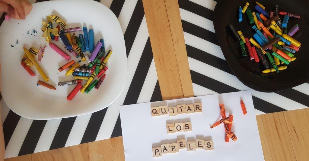 dos platos con ceras rotas, las manos de mi hijo quitando el papel que envuelve a las ceras  algunas sobre el plato y fichas de scrabble de madera formando el texto quitar los papeles