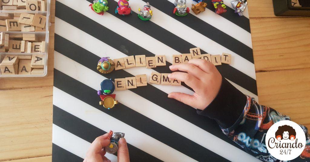 Las manos de mi hijo de 6 años, una sostiene un superzing y la otra está sobre unas letras de scrabble de madera donde dice alien bandit y enigma al lado de esos muñequitos. se ven más superzings y una caja con más letras. logo de criando 24/7