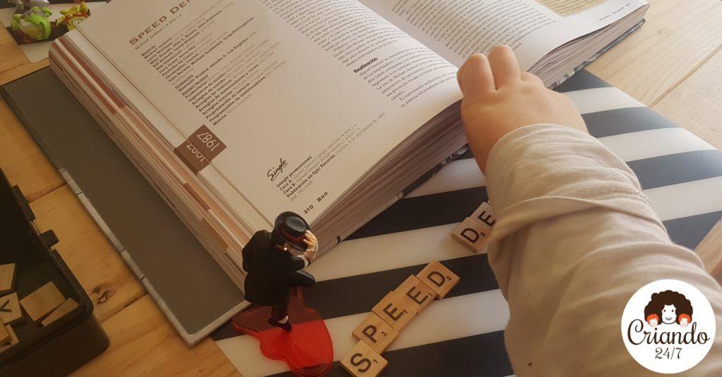 Mi hijo de 8 años con un libro de michael jackson, una figura pequeña de MJ mientras escribe con letras de scrabble de madera speed demon. logo de criando 24/7