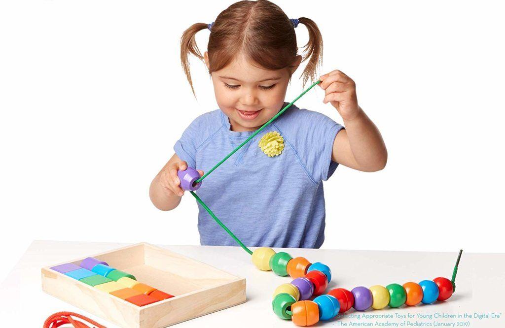 niñas jugando con un juego de ensartar cuentas de colores de madera