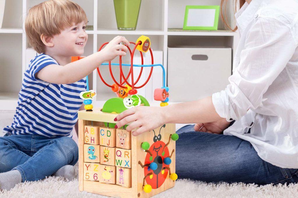 madre e hijo en el suelo jugando con un juguete con forma de cubo de madera con diferentes actividades de motricidad fina