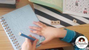 mi hijo de 6 años escribiendo en un cuaderno con un lapiz, a su lado unas letras de scrabble de ,adera con la palabra AMA. logo de criando 24/7