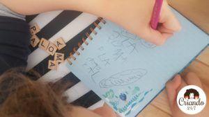 mi hijo de 8 años con hemiparesia derecha, escribiendo con la mano izquierda en su cuaderno usando un lapiz gordo con forma triangular, y varias letras de madera de scrabble a su lado. logo de criando 24/7