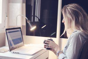 Psicóloga Charo Poggi en su despacho, mirando el portatil con una taza de café en la mano